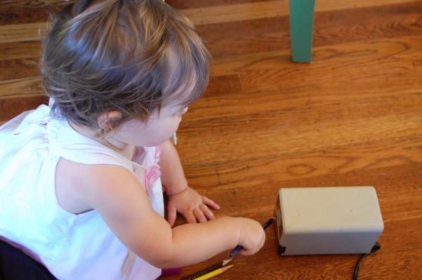 toddler sharpens pencils