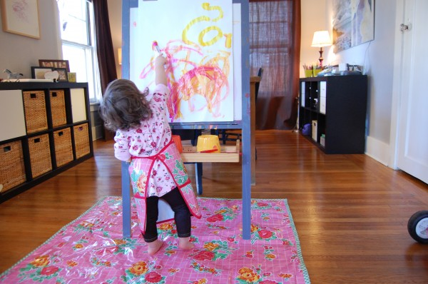 one year old painting at the easel
