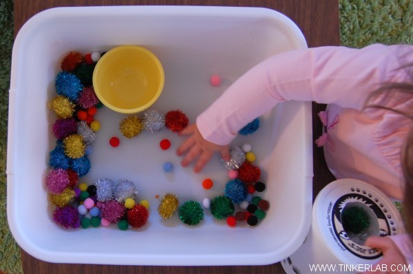 toddler scooping pom poms