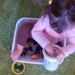 toddler sitting in plastic container with pom poms