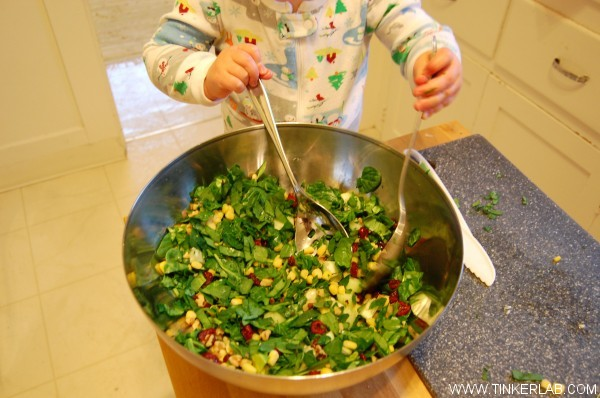 toddler mixing salad