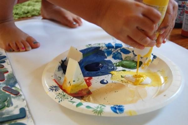 child squeezing paint