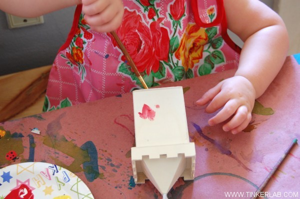 toddler painting birdhouse