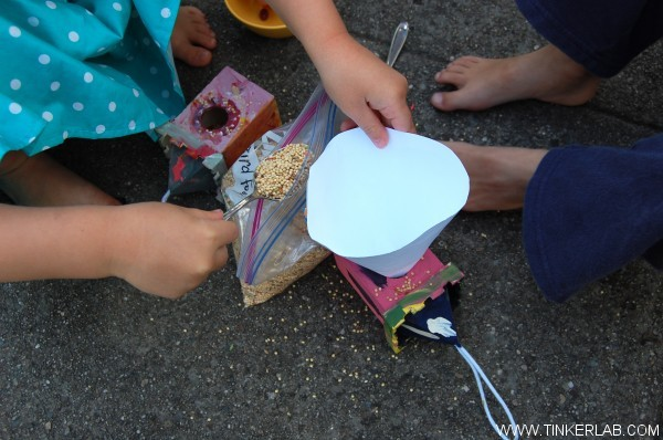 filling birdhouse with seed