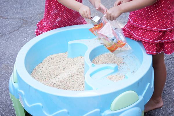 sensory table with bird seed scooping